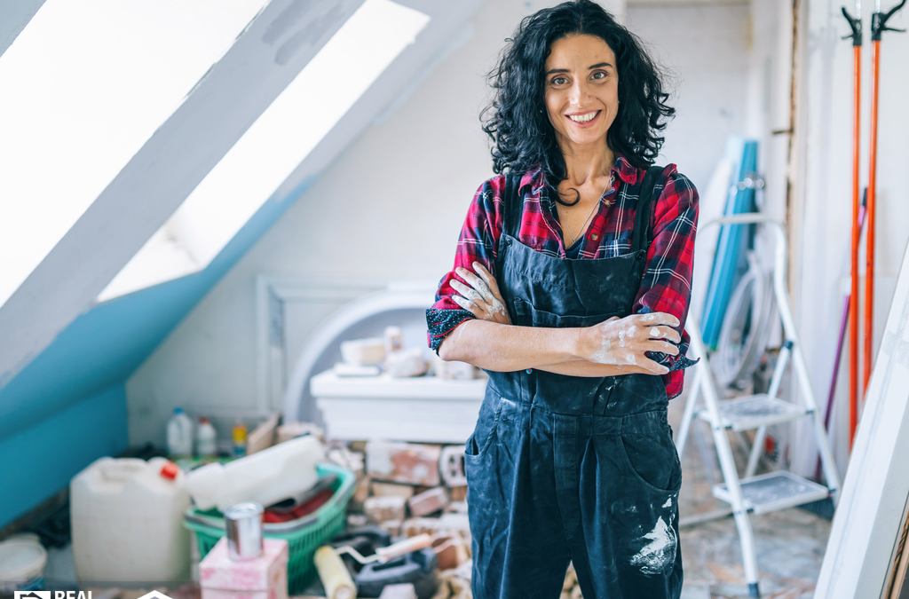 a woman in overalls painting a messy house interior